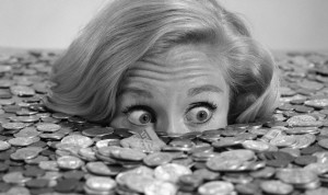 08 Jun 1966 --- 1960s Bug-Eyed Surprised Woman Buried In Coins Money Symbolic --- Image by © H. Armstrong Roberts/ClassicStock/Corbis
